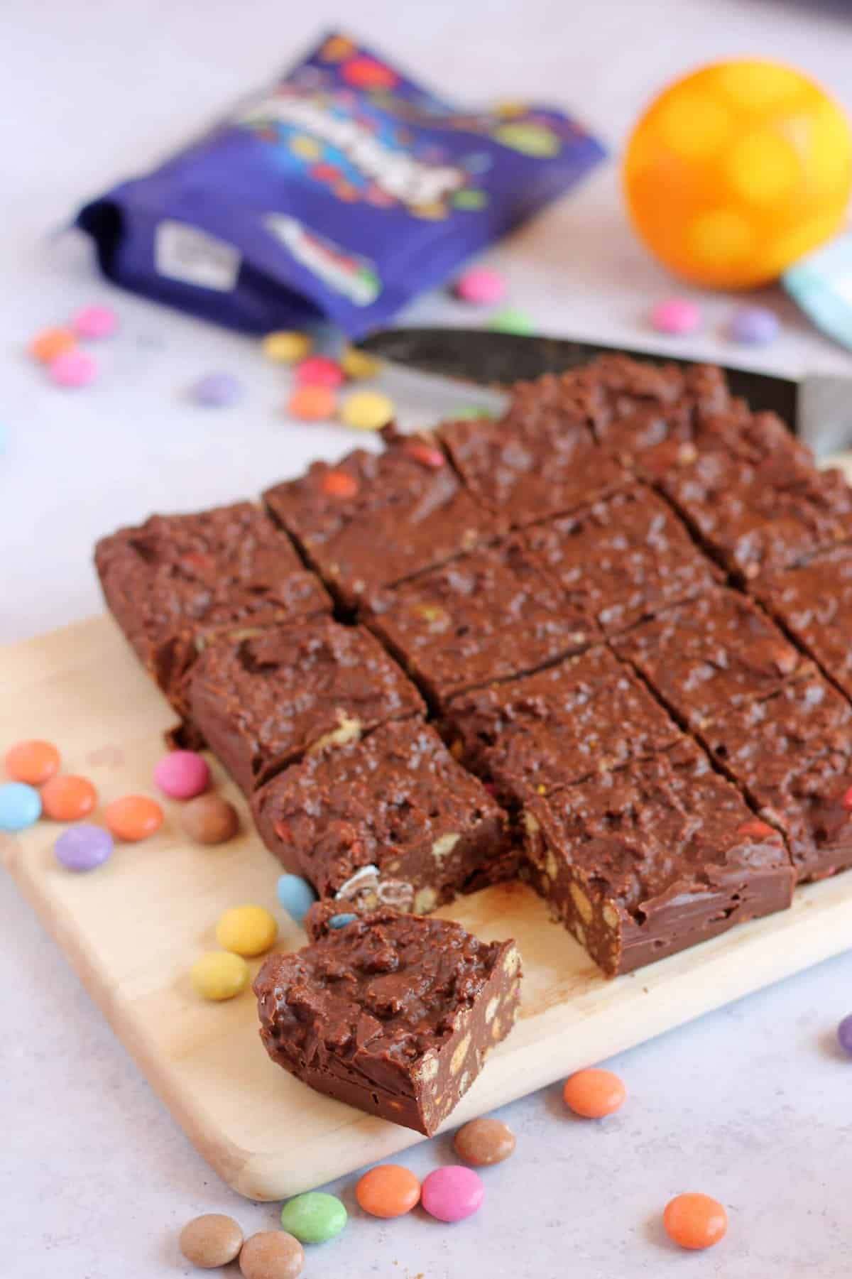 Chocolate biscuit cake, cut into squares on a chopping board.