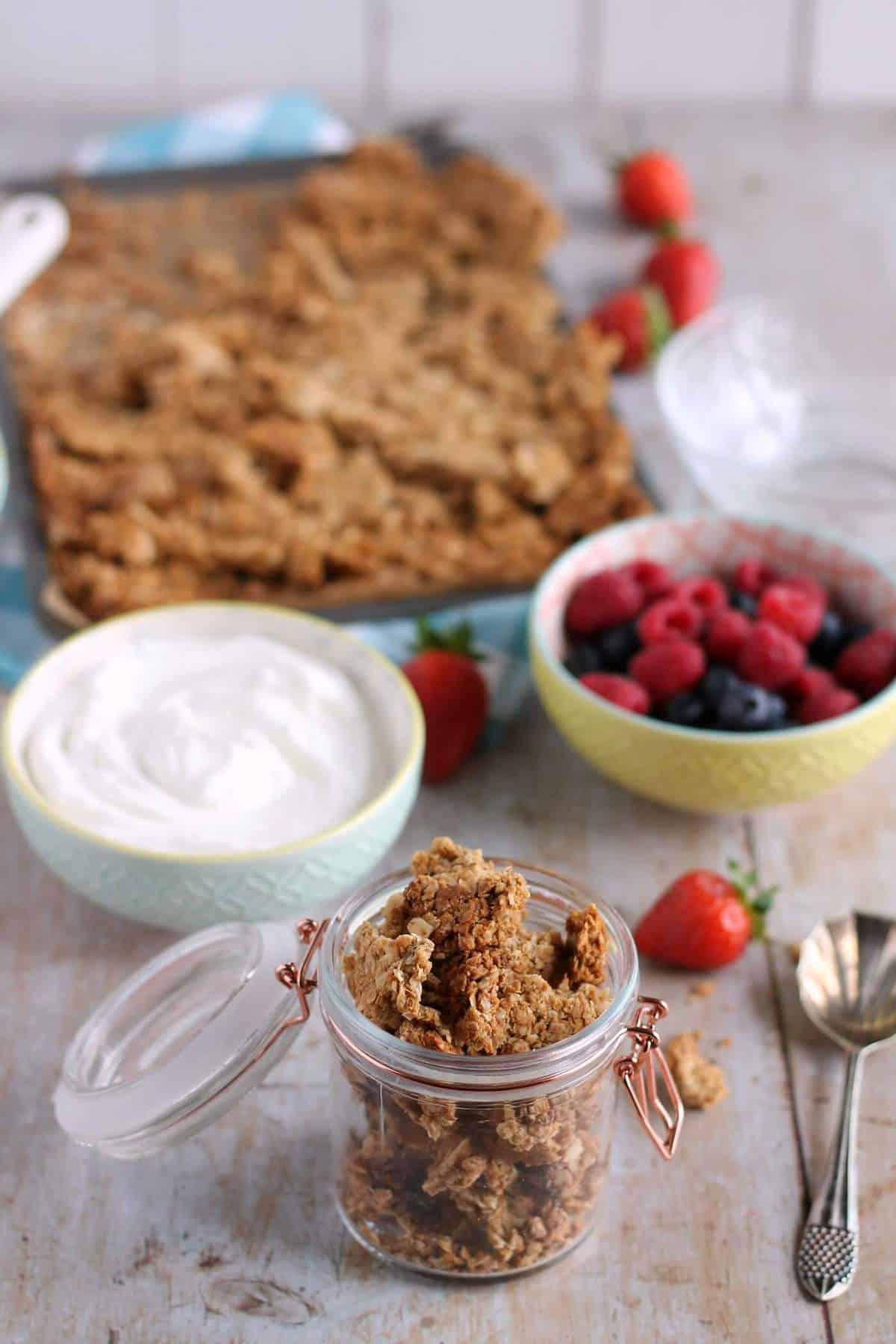 A kilner jar full of homemade peanut butter granola, with yogurt and fresh berries
