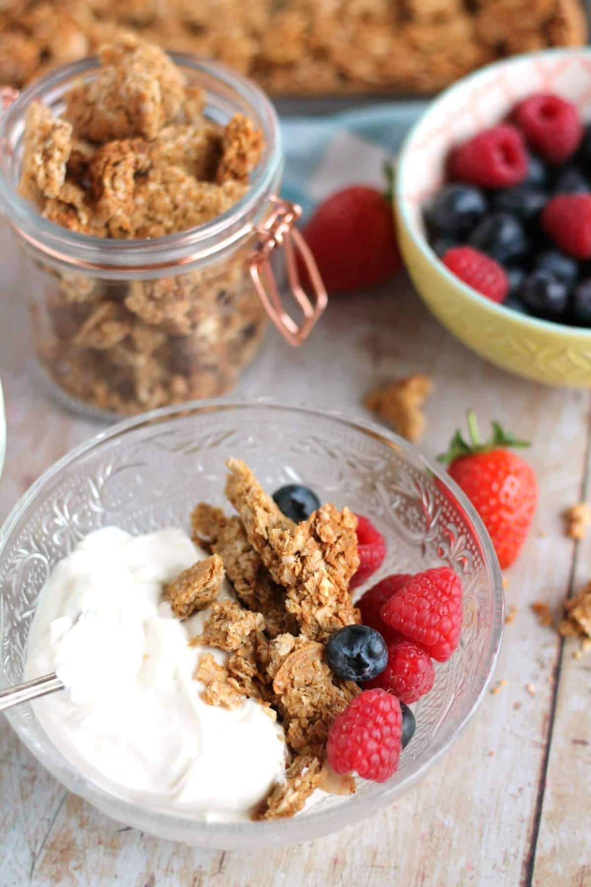 A bowl of homemade crunchy peanut butter granola with yogurt and berries.