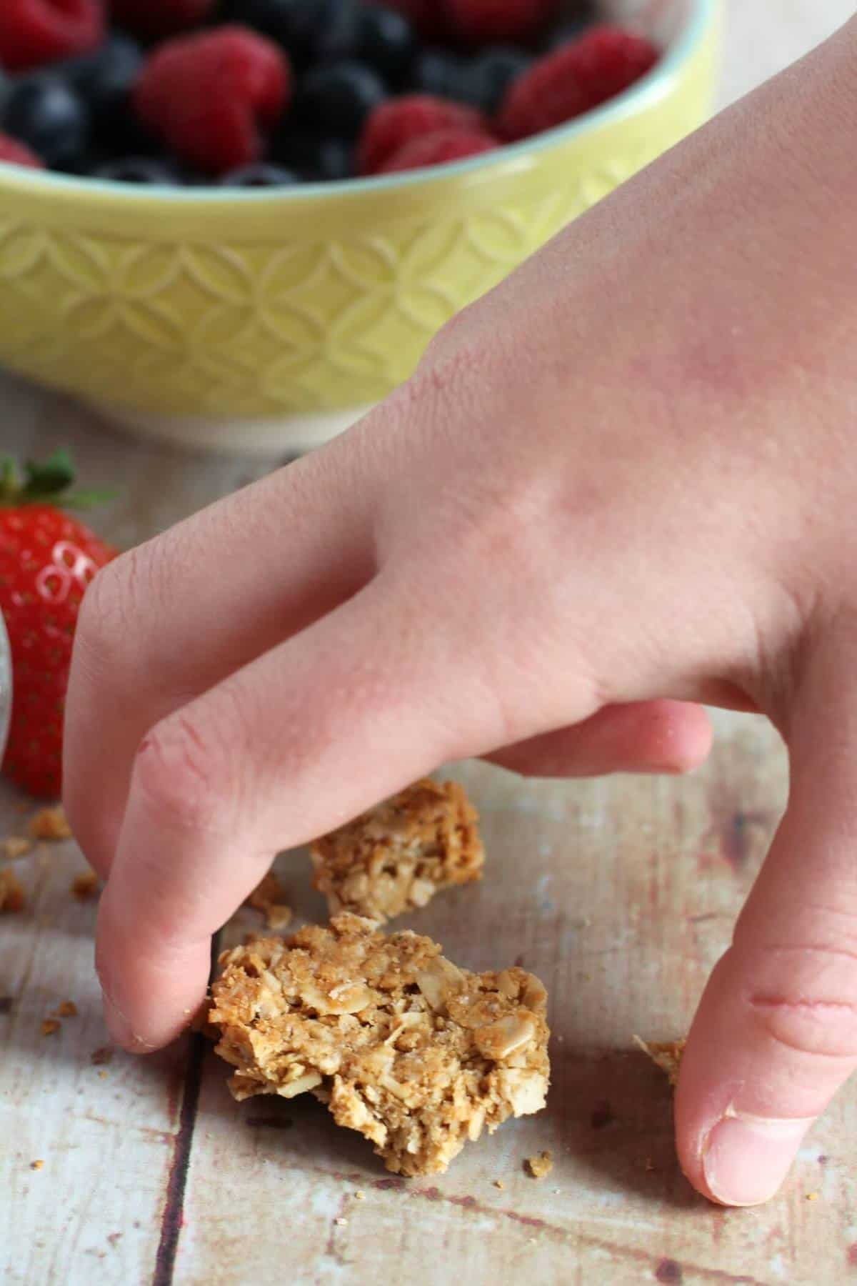 Child's hand picking up a piece of chunky granola