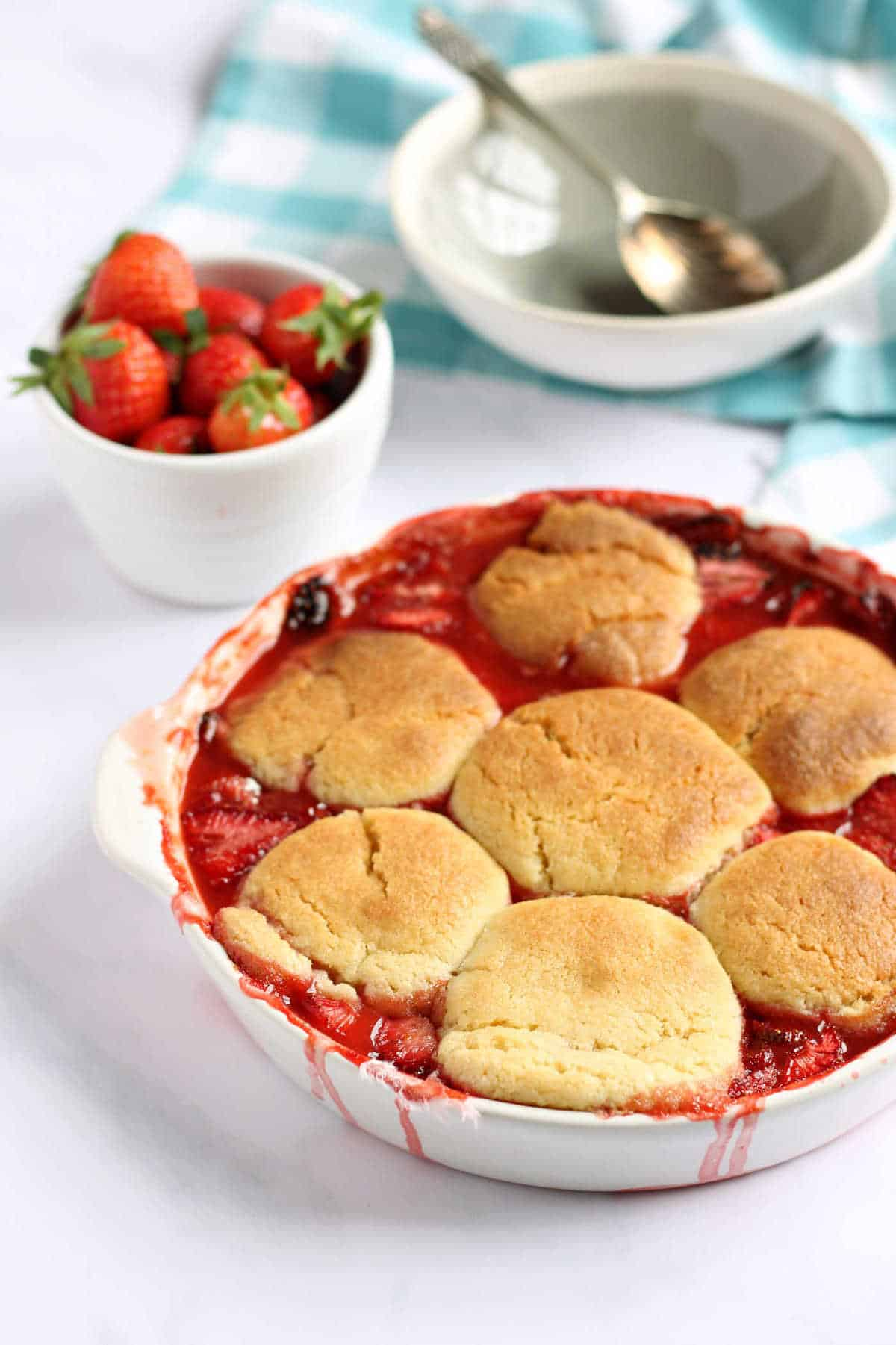 This easy strawberry cobbler recipe is a delicious summery dessert, that celebrates strawberry season in style. The golden cobbler topping encases sweet juicy strawberries underneath. Serve warm with ice-cream for a taste of summer, whatever the time of year.