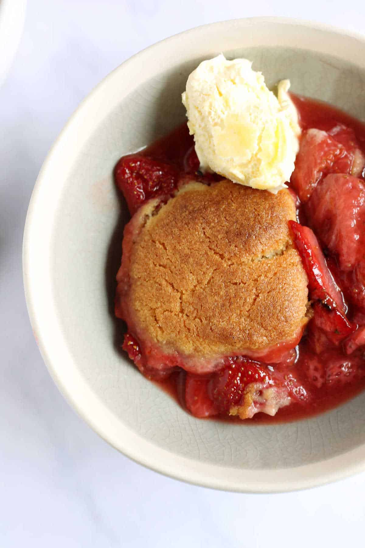 An overhead shot of a bowl of strawberry cobbler with clotted cream