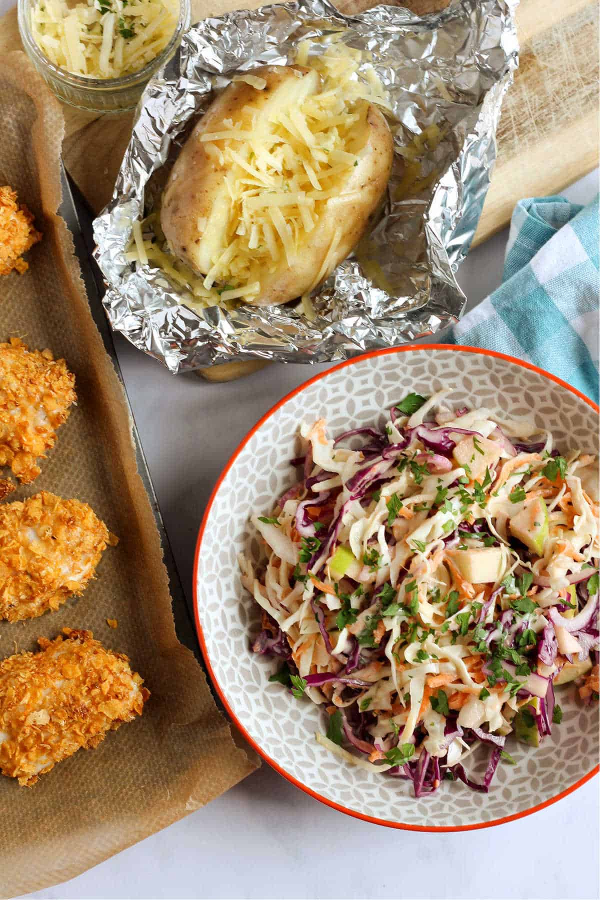 Apple coleslaw in a bowl with a baked potato and cornflake chicken nuggets