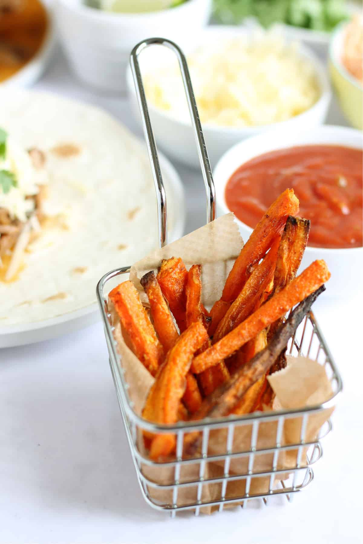 A portion of baked carrot fries with homemade ketchup