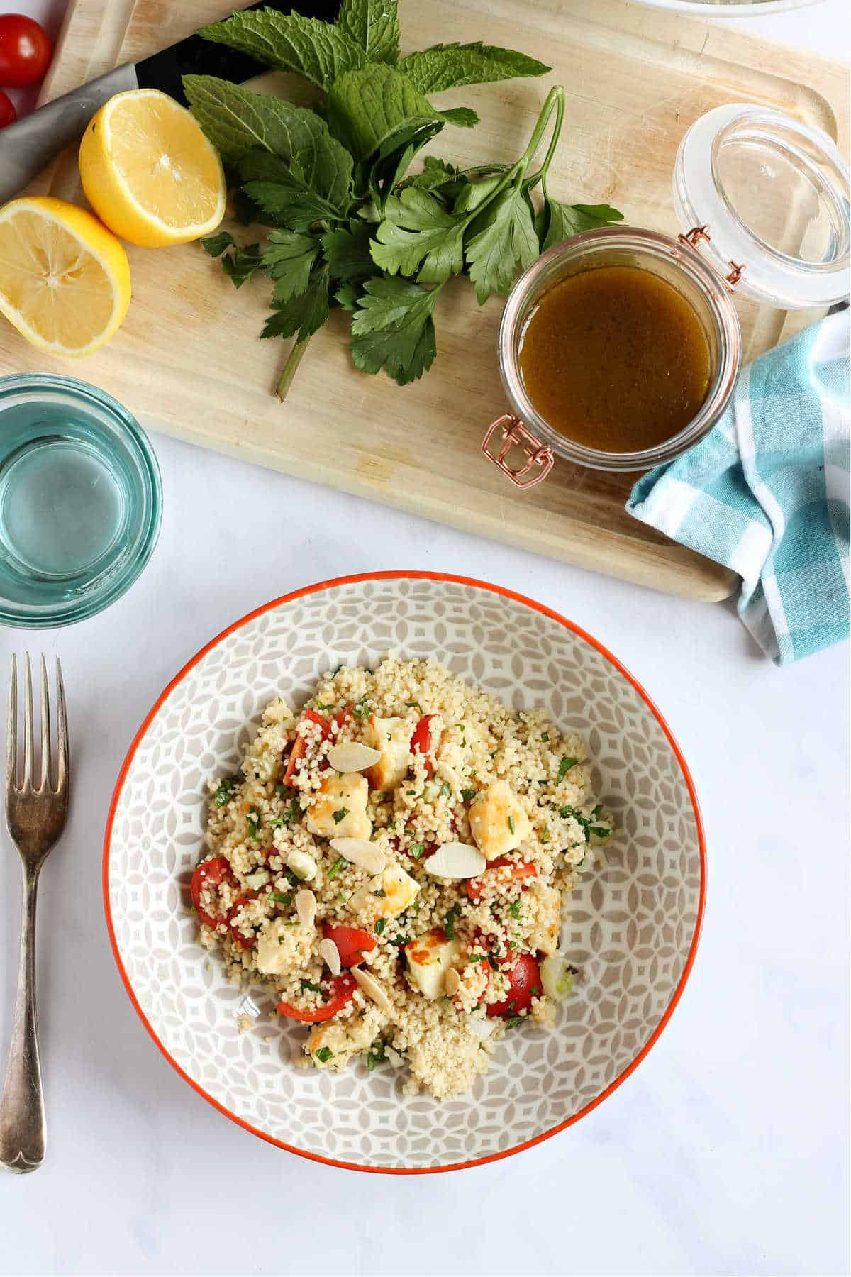Overhead shot of couscous salad with salad dressing.