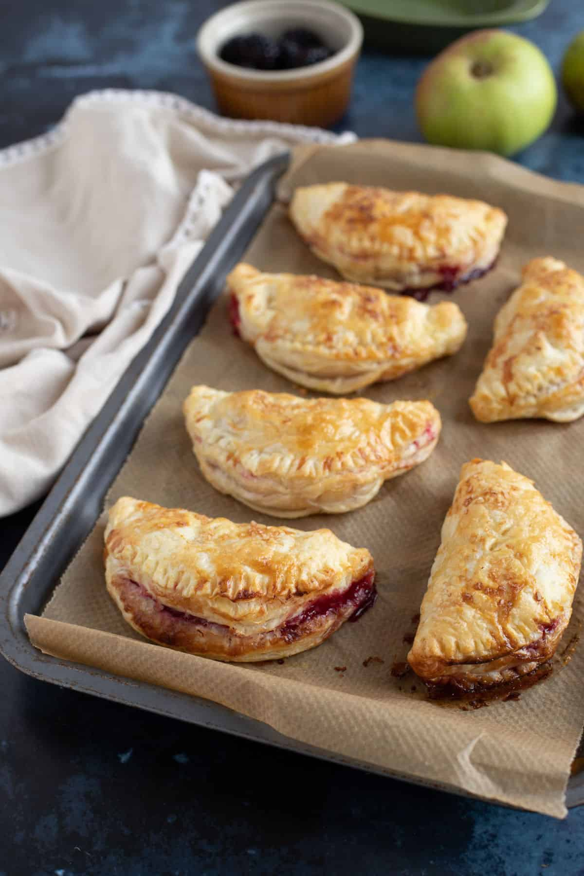 6 apple and blackberry turnovers on a baking tray with cooking apples in the background.