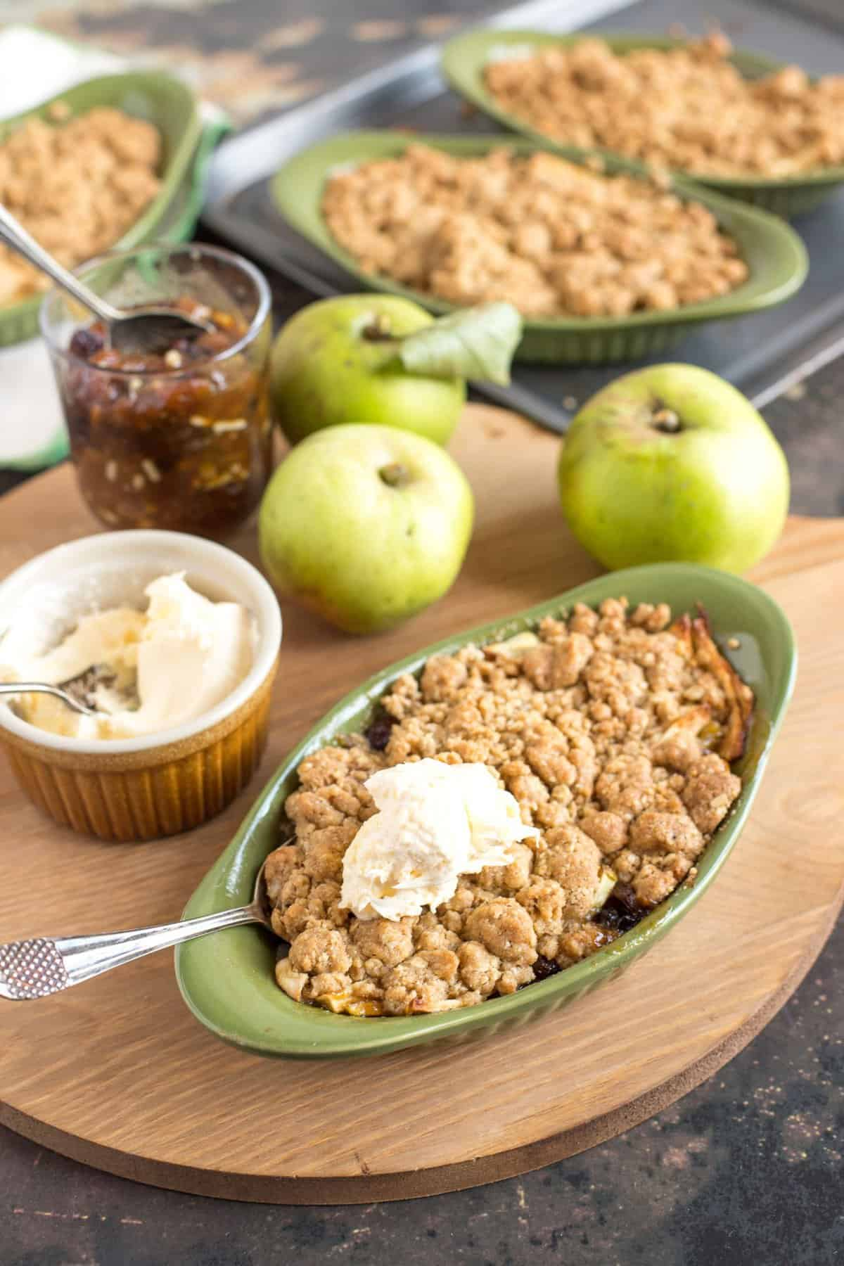 An individual serving of Apple and Mincemeat Crumble with clotted cream on top.