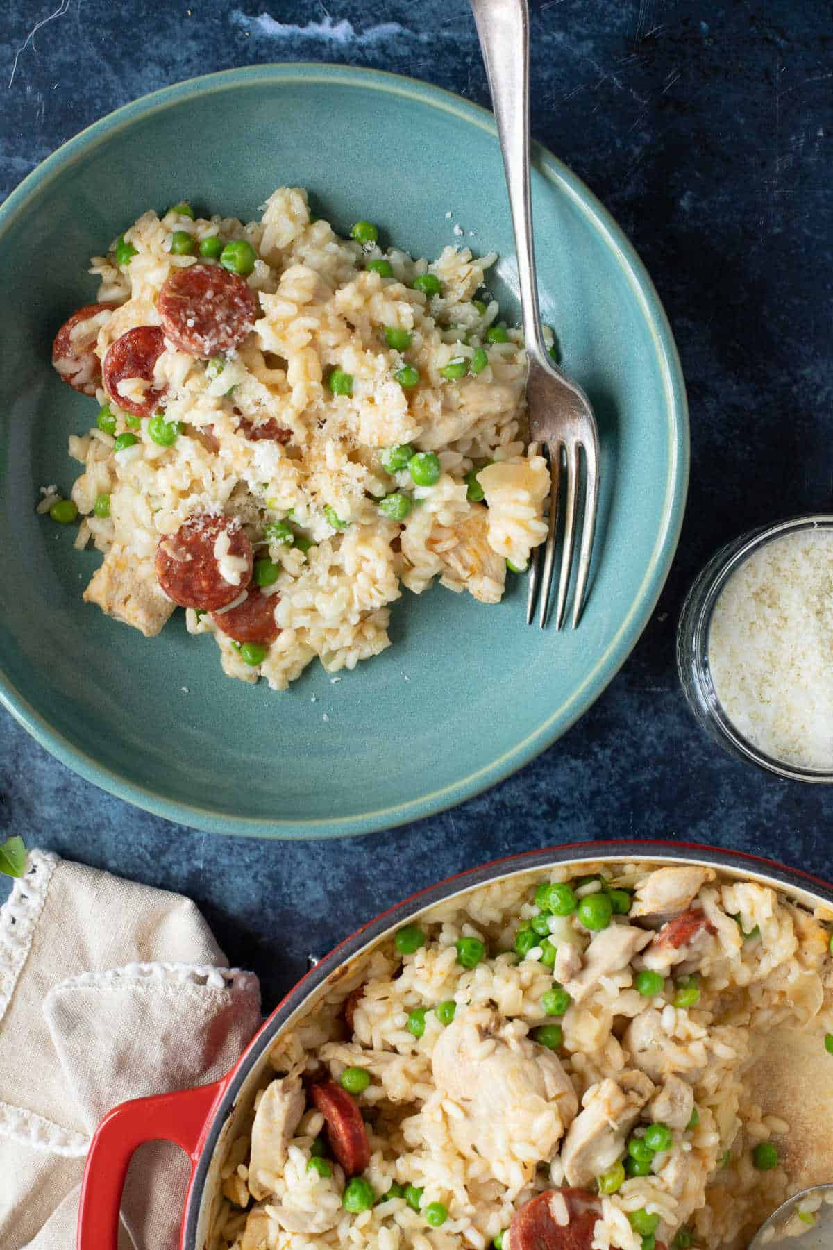 A bowl of oven baked risotto sprinkled with grated Parmesan.