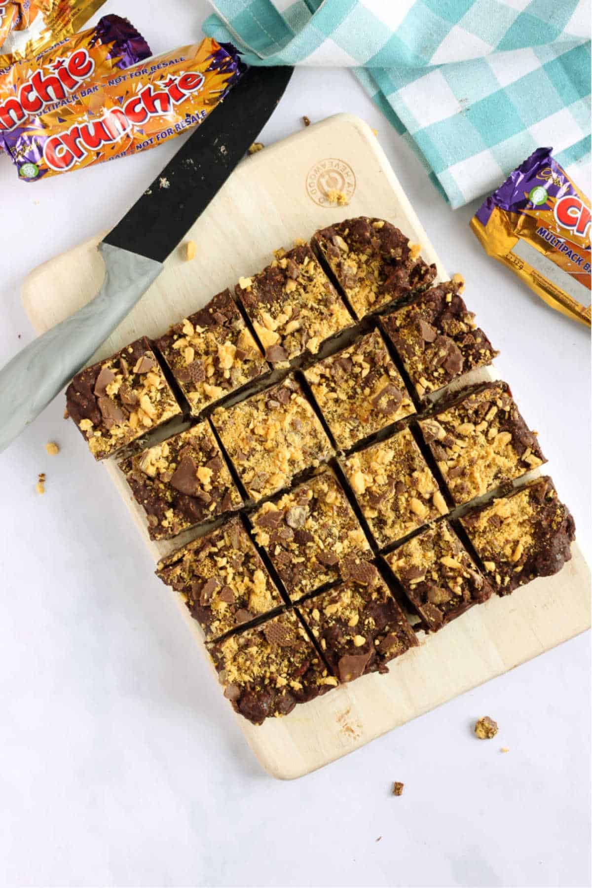 Overhead shot of chocolate crunchie tiffin, cut into squares with a grey knife.
