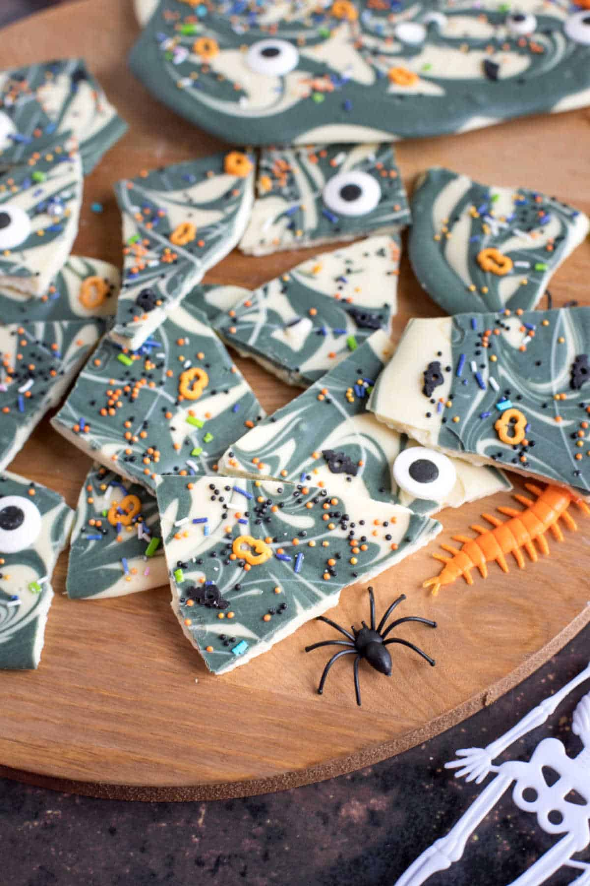 Broken pieces of chocolate bark decorated for Halloween with sprinkles and edible eyes.