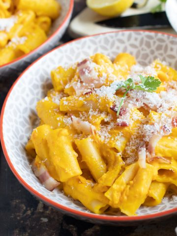 Bacon and pumpkin pasta in a bowl.