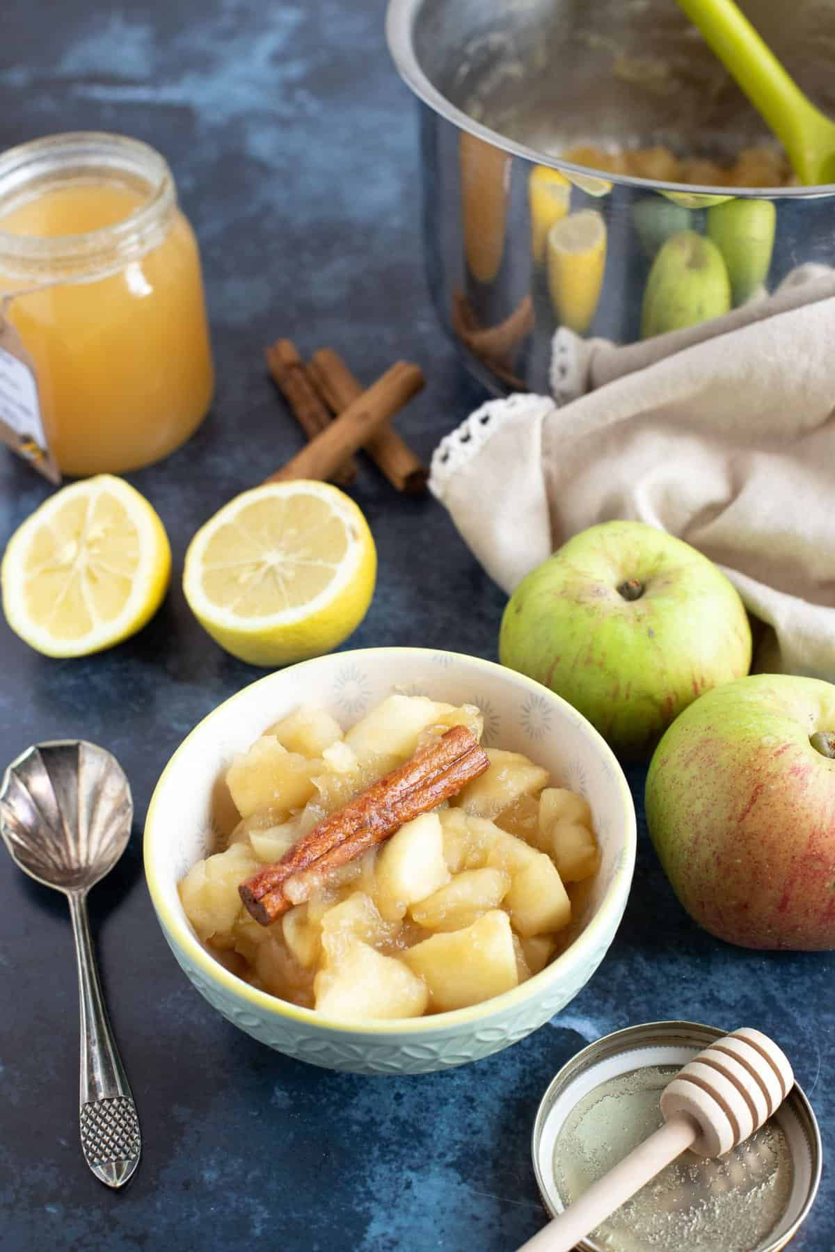 Stewed apples in a bowl with a pan of stewed apples behind.