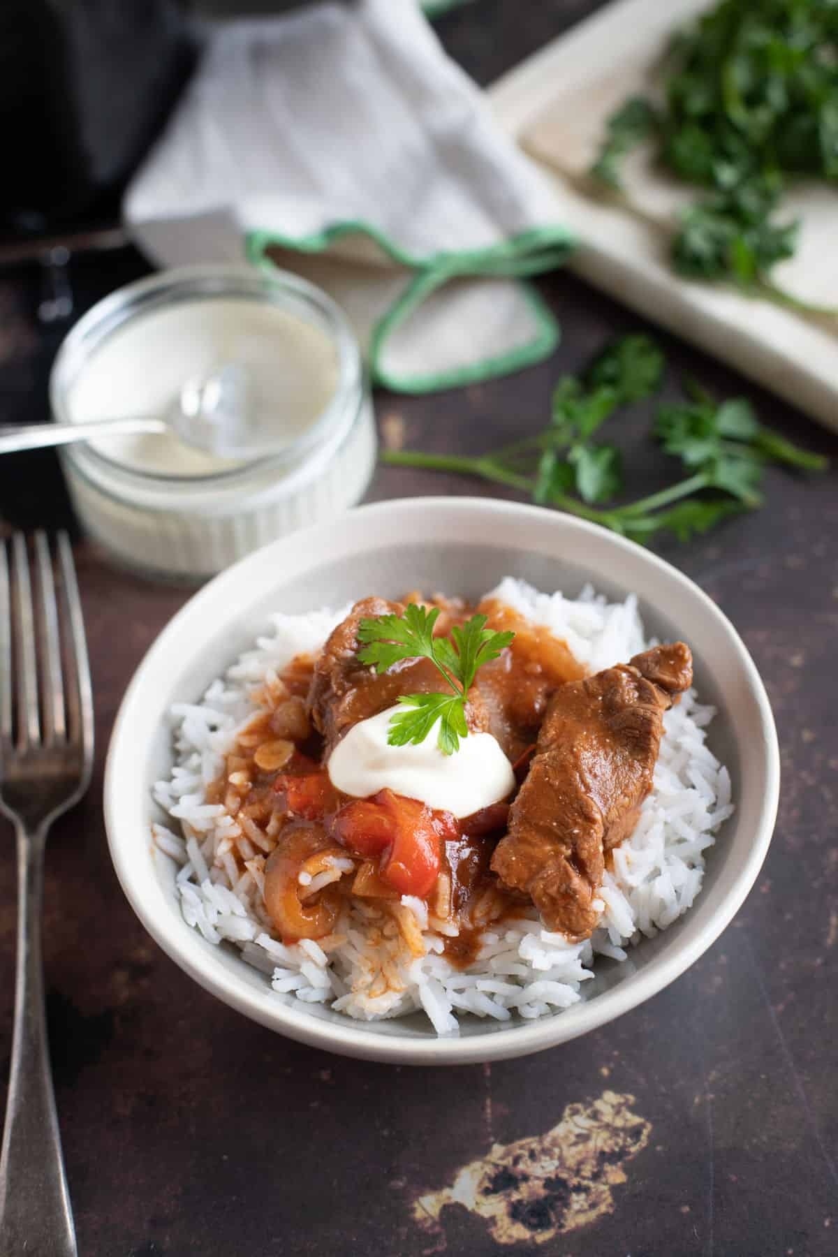 Slow cooker beef goulash served on a bed of rice with soured cream and parsley.