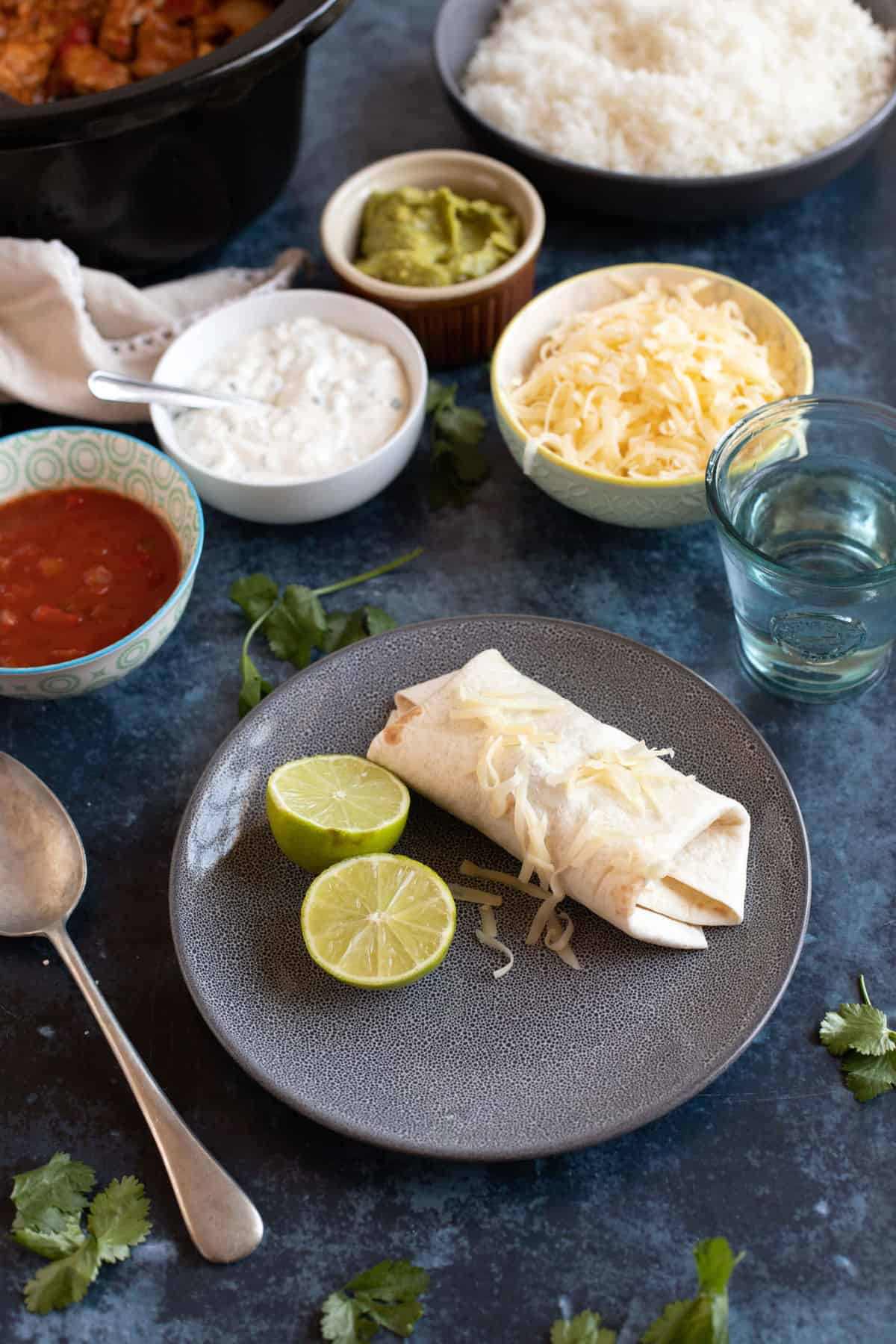 A fajita wrap on a plate with grated cheddar, sour cream and salsa.
