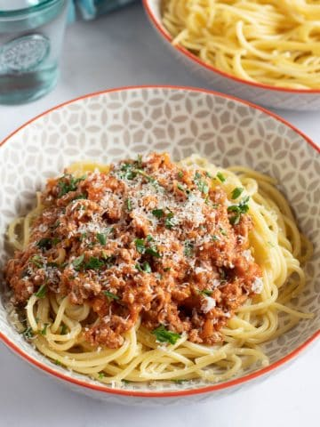 turkey bolognese in a bowl with grated parmesan.