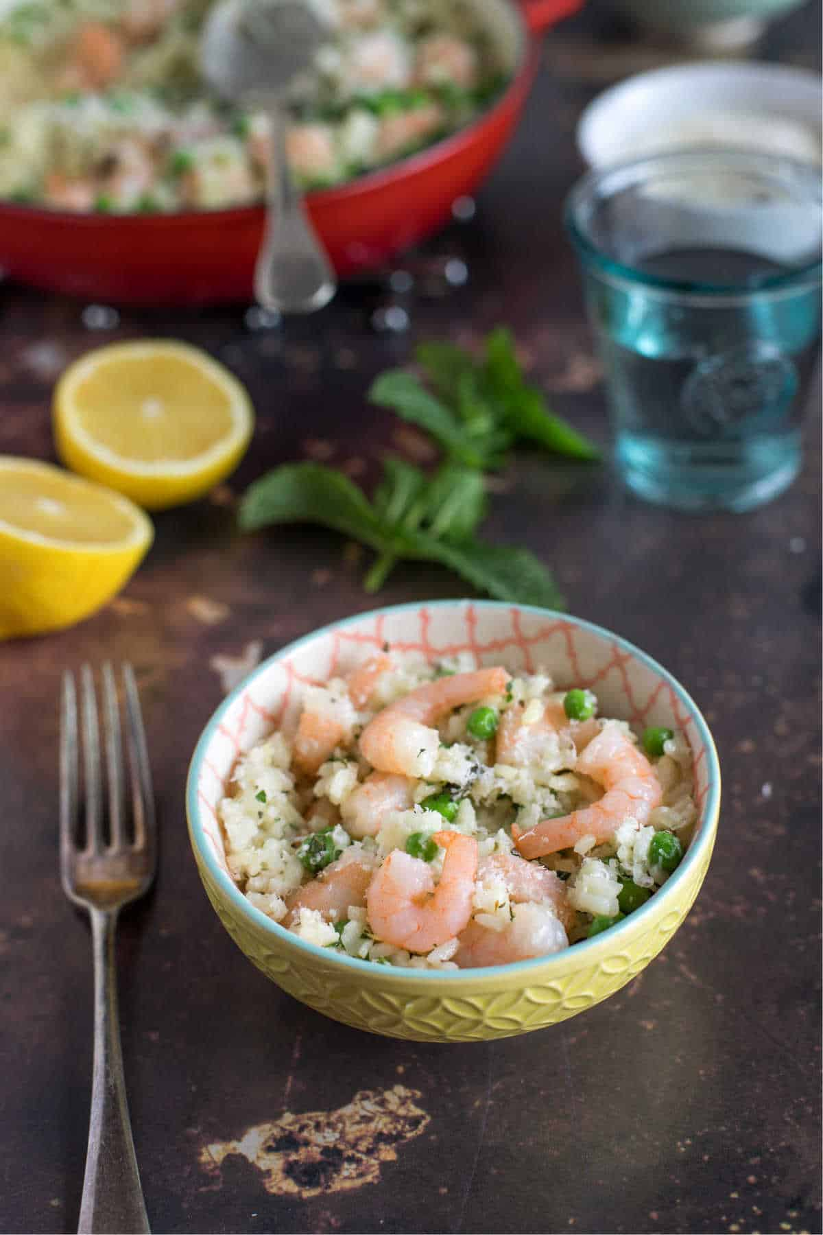 A bowl of prawn and pea risotto with lemon.
