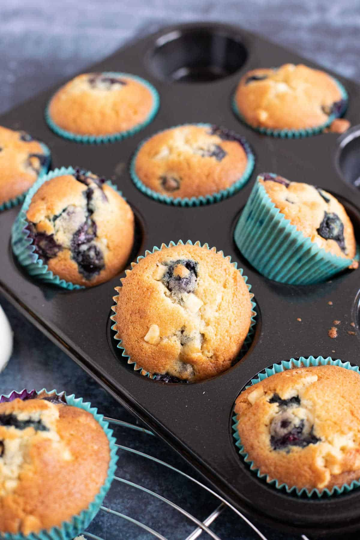 A tray of blueberry muffins with white chocolate chips.