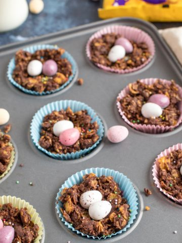 Chocolate cornflake cakes in a muffin pan with mini eggs.