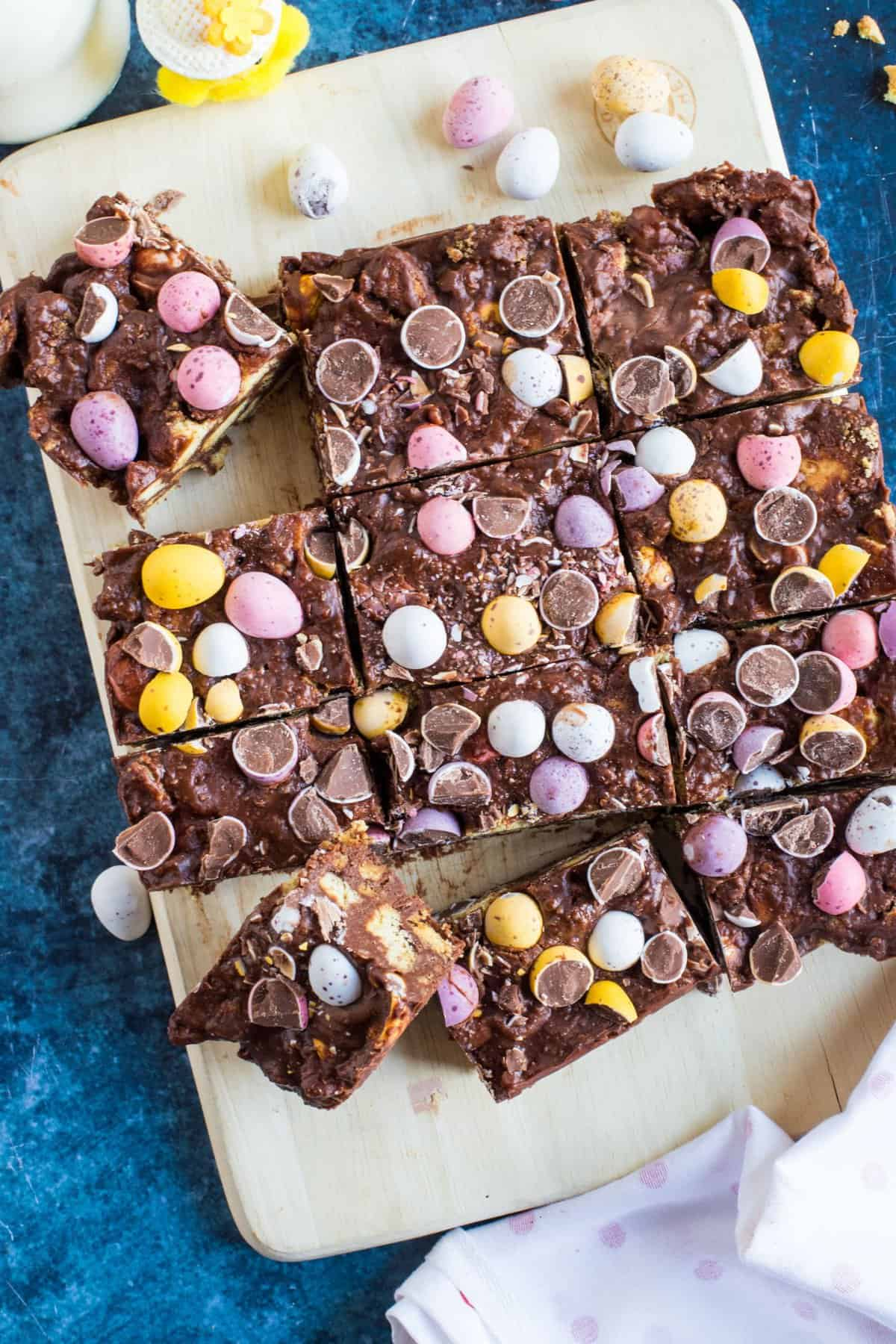 This no-bake chocolate mini egg tiffin is the perfect chocolate treat for Easter, or any time of year for that matter! Crushed digestive biscuits, melted dark and milk chocolate and sweet golden syrup encase the all-important Cadburys mini eggs in this decadent chocolate delight. Not for the faint-hearted, that's for sure!
