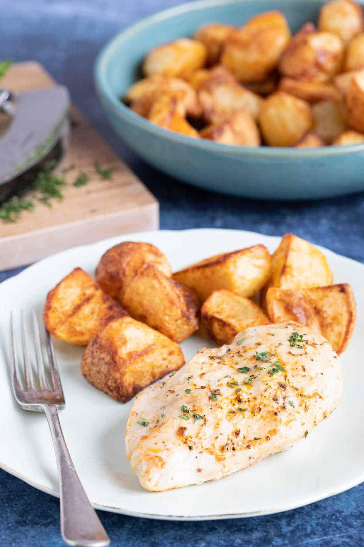 Air fryer Italian chicken breast served with air fryer roast potatoes.