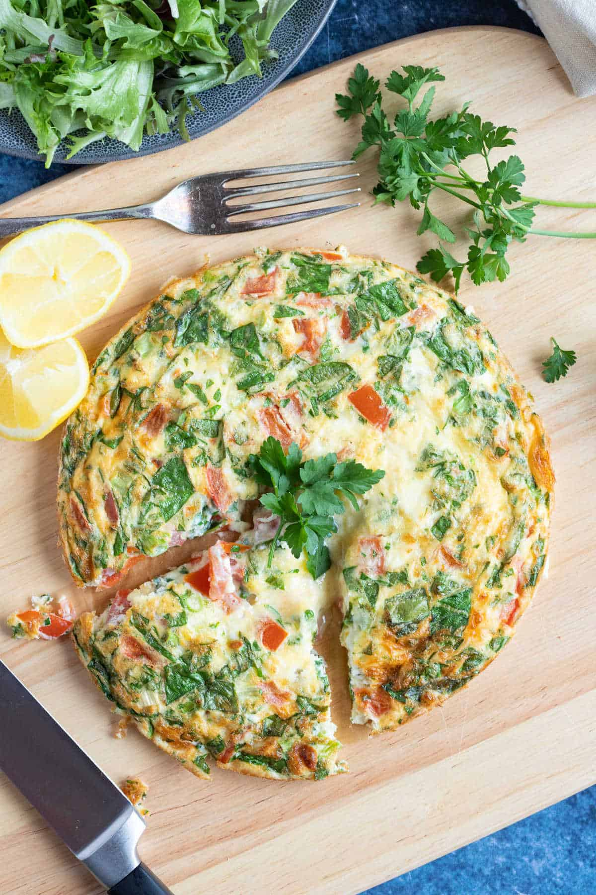 Sliced air fryer breakfast frittata with tomatoes and spinach.
