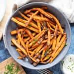 A bowl of seasoned air fryer sweet potato fries.