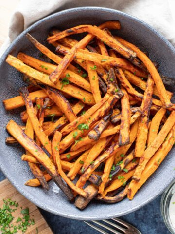 A bowl of seasoned air fryer sweet potato fries.