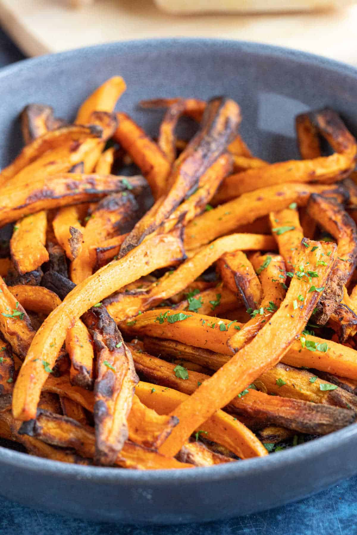Sweet potato fries in a grey bowl served with chopped parsley.
