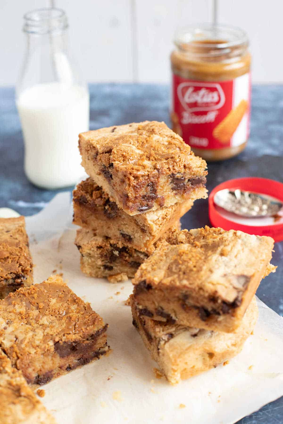 Cut blondies on a wooden board with a glass of milk in the background.