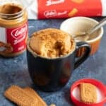 Biscoff mug cake in a large black mug sprinkled with lotus biscuit crumbs.