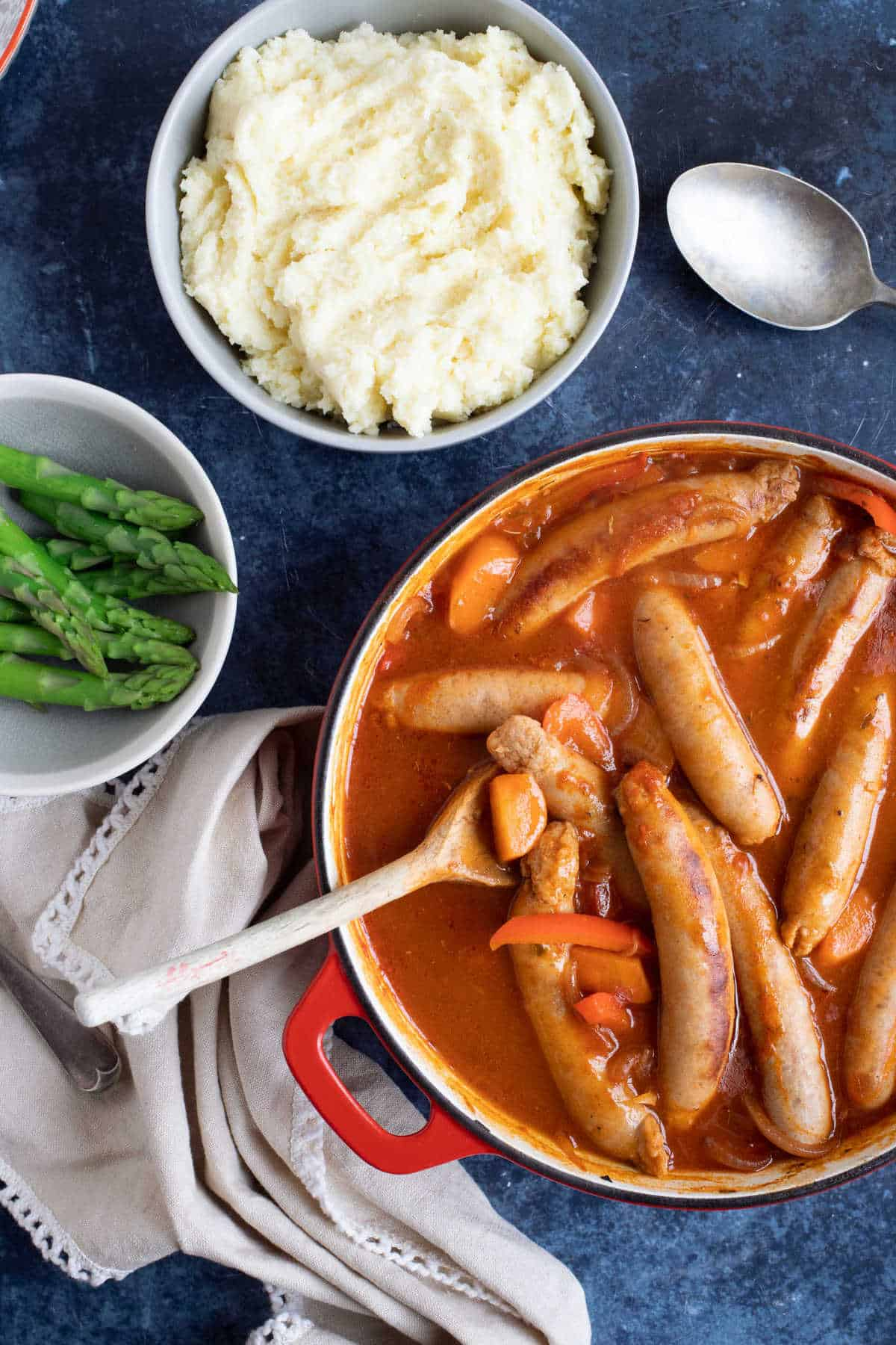 Sausage casserole with mashed potato and asparagus.