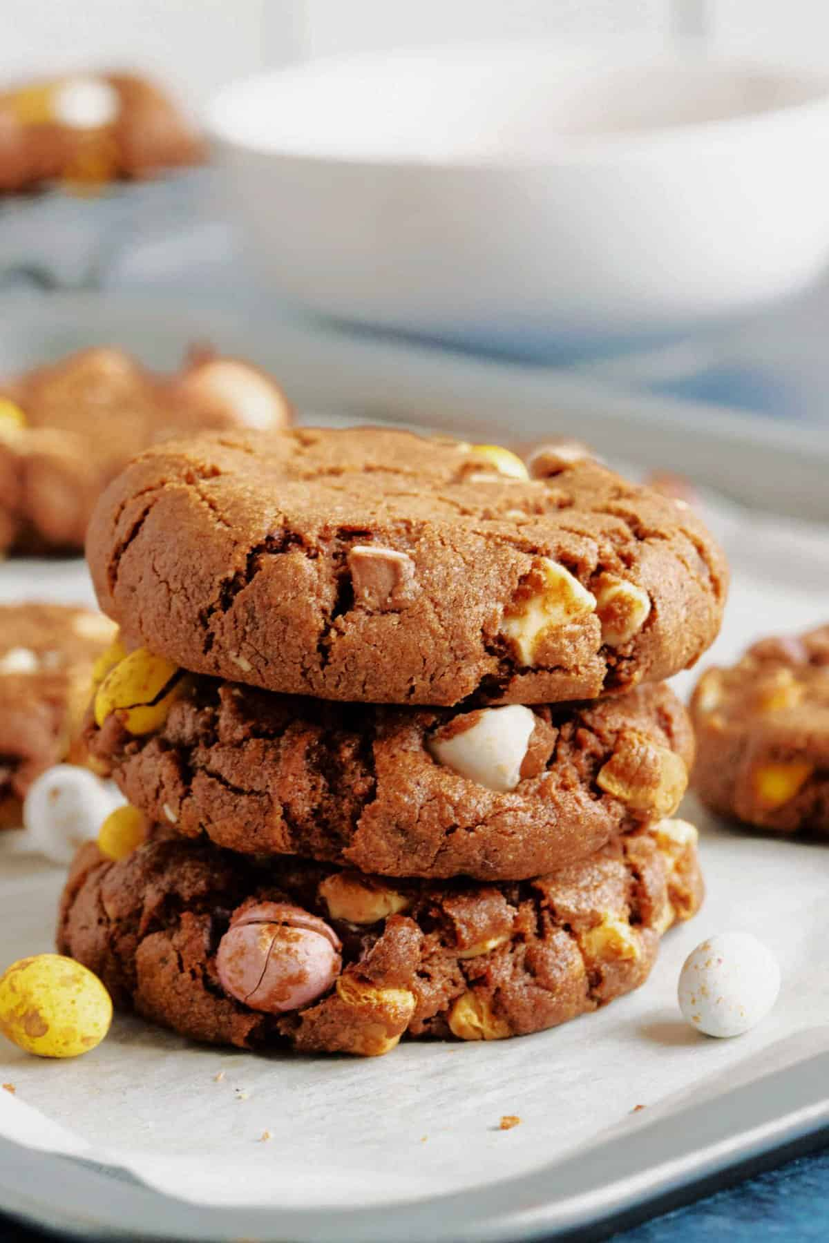 3 chocolate mini egg cookies on a baking sheet.