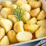 Crispy polenta roast potatoes in a roasting tin.