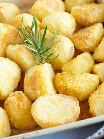 Crispy polenta roast potatoes in a roasting tin.