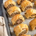 Puff pastry sausage rolls on a baking sheet.