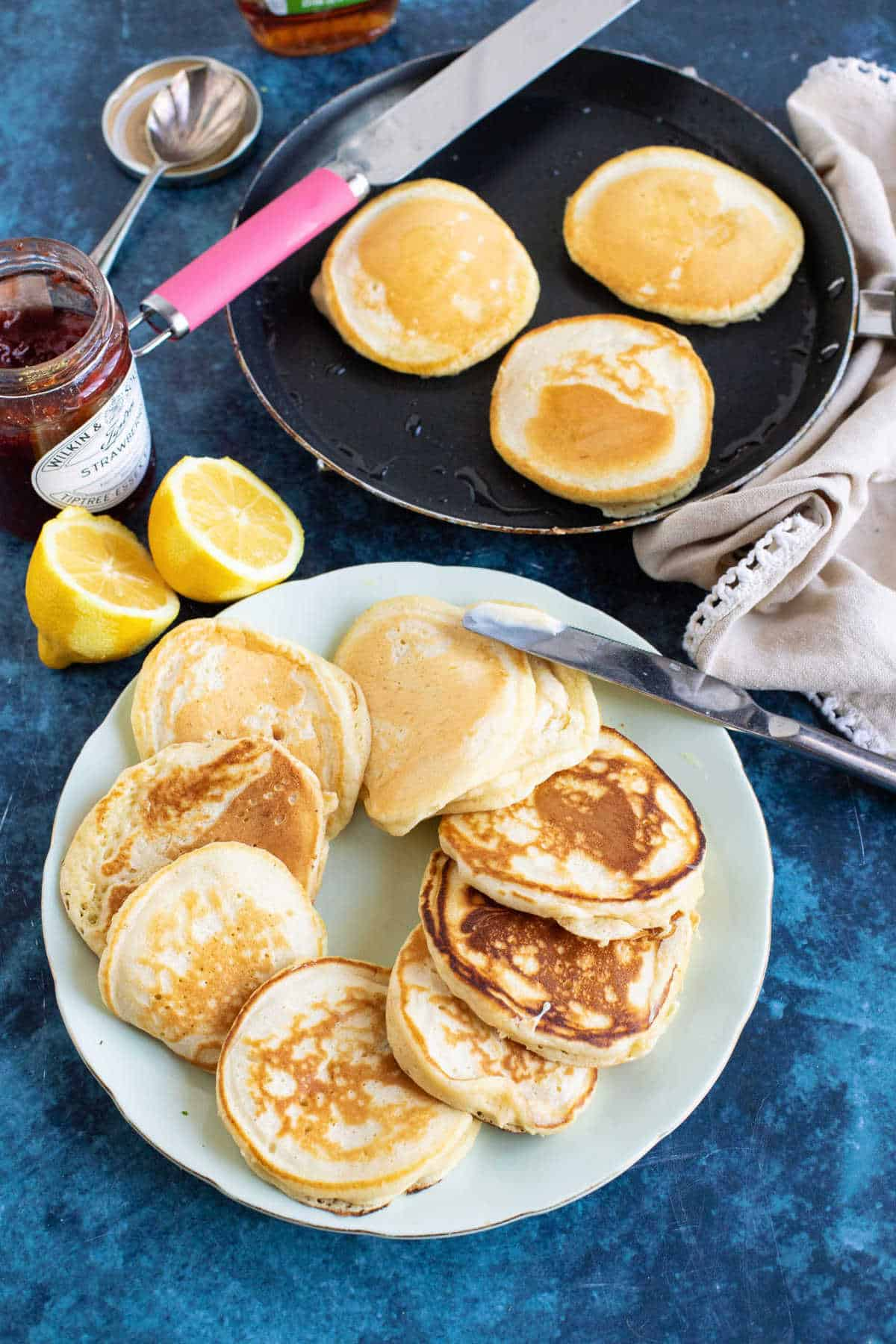 Drop scones served on a plate with butter and jam.