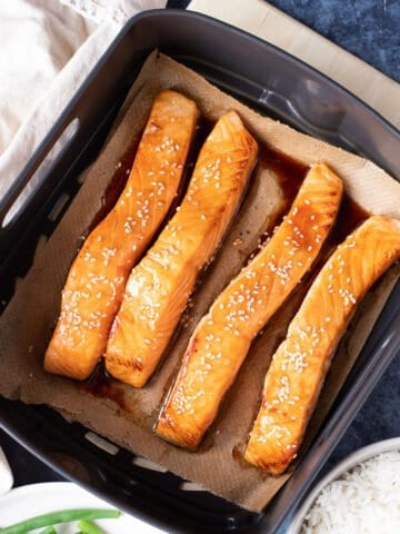 salmon fillets in an air fryer basket.