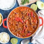 A pan of mild chilli with lime wedges, rice and tortilla chips.