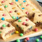 M&M Cookie Bars cut into slices on a board.