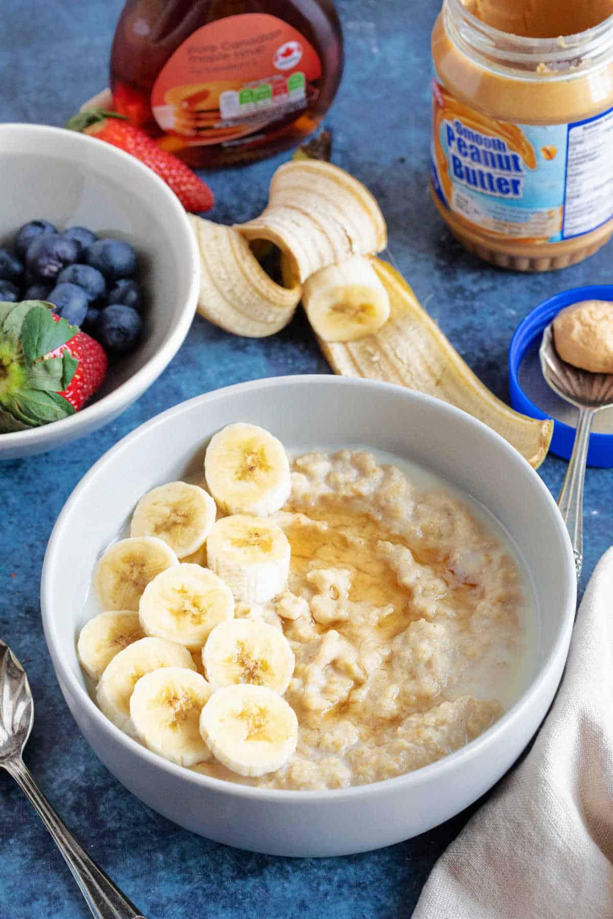 A bowl of peanut butter porridge with sliced banana.