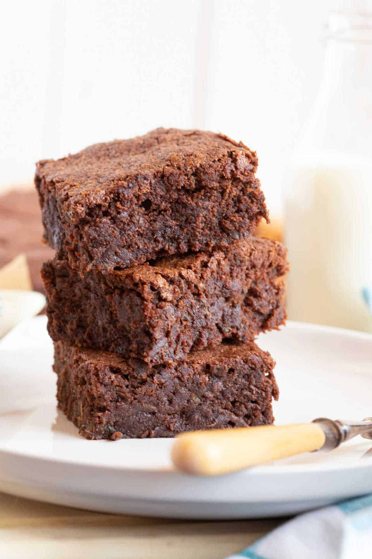 A stack of three courgette brownies on a plate.