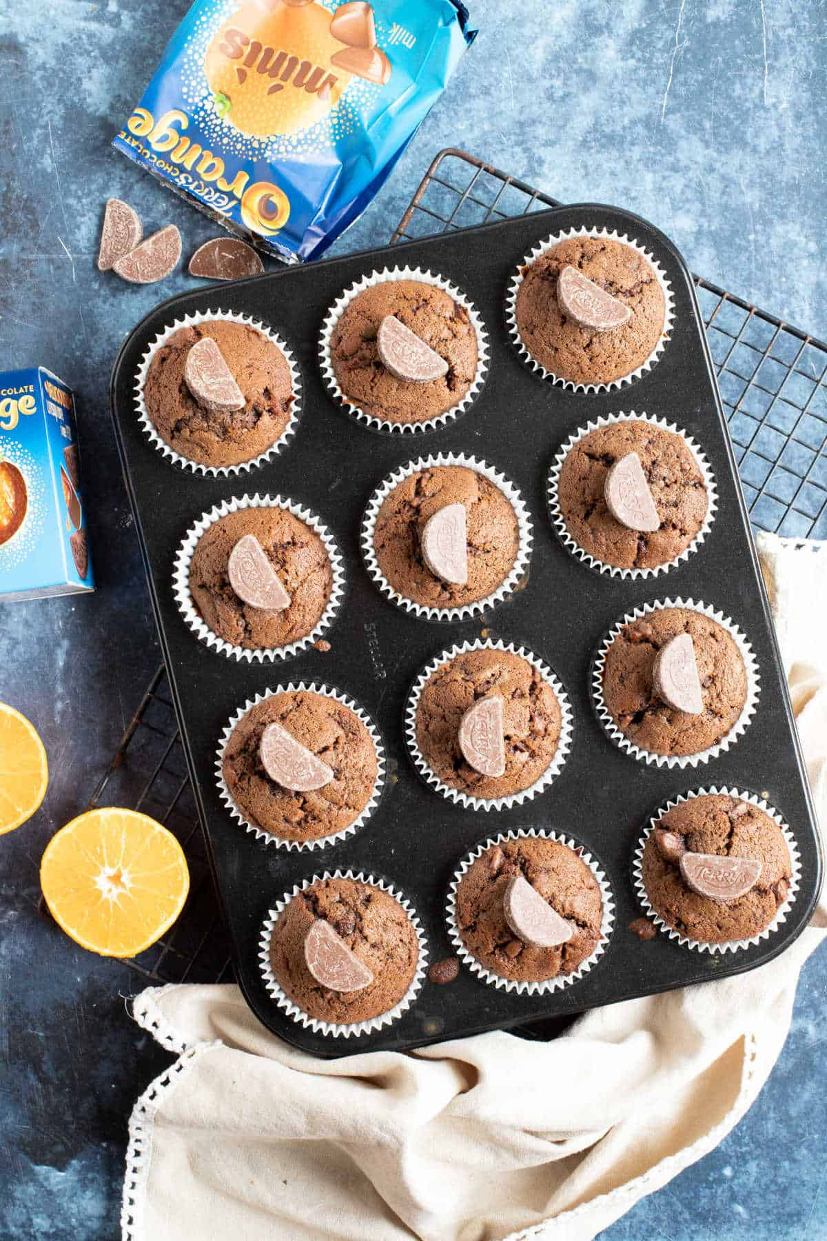 Chocolate orange muffins in a baking tin.