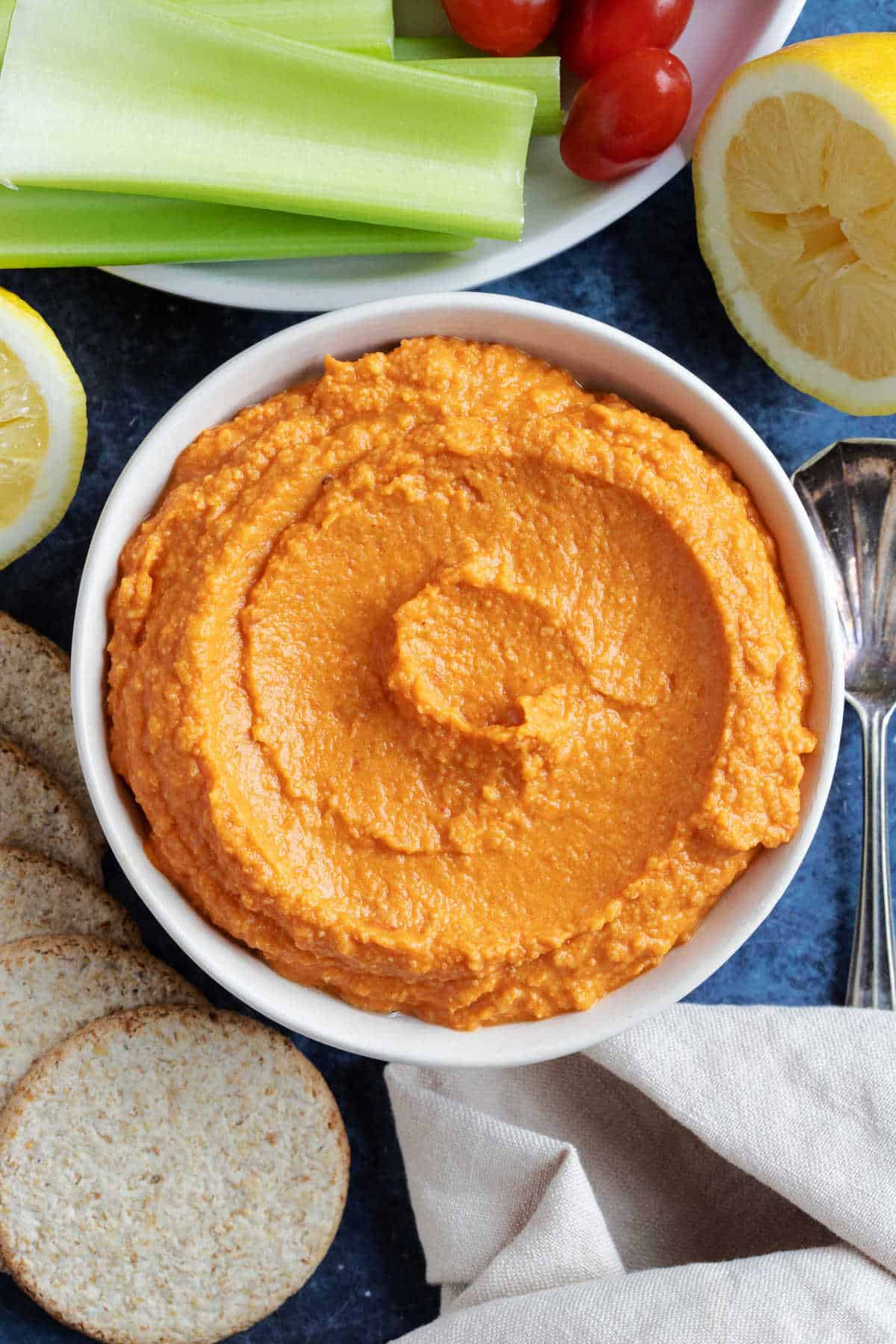 Roasted red pepper hummus in a serving dish with celery sticks.