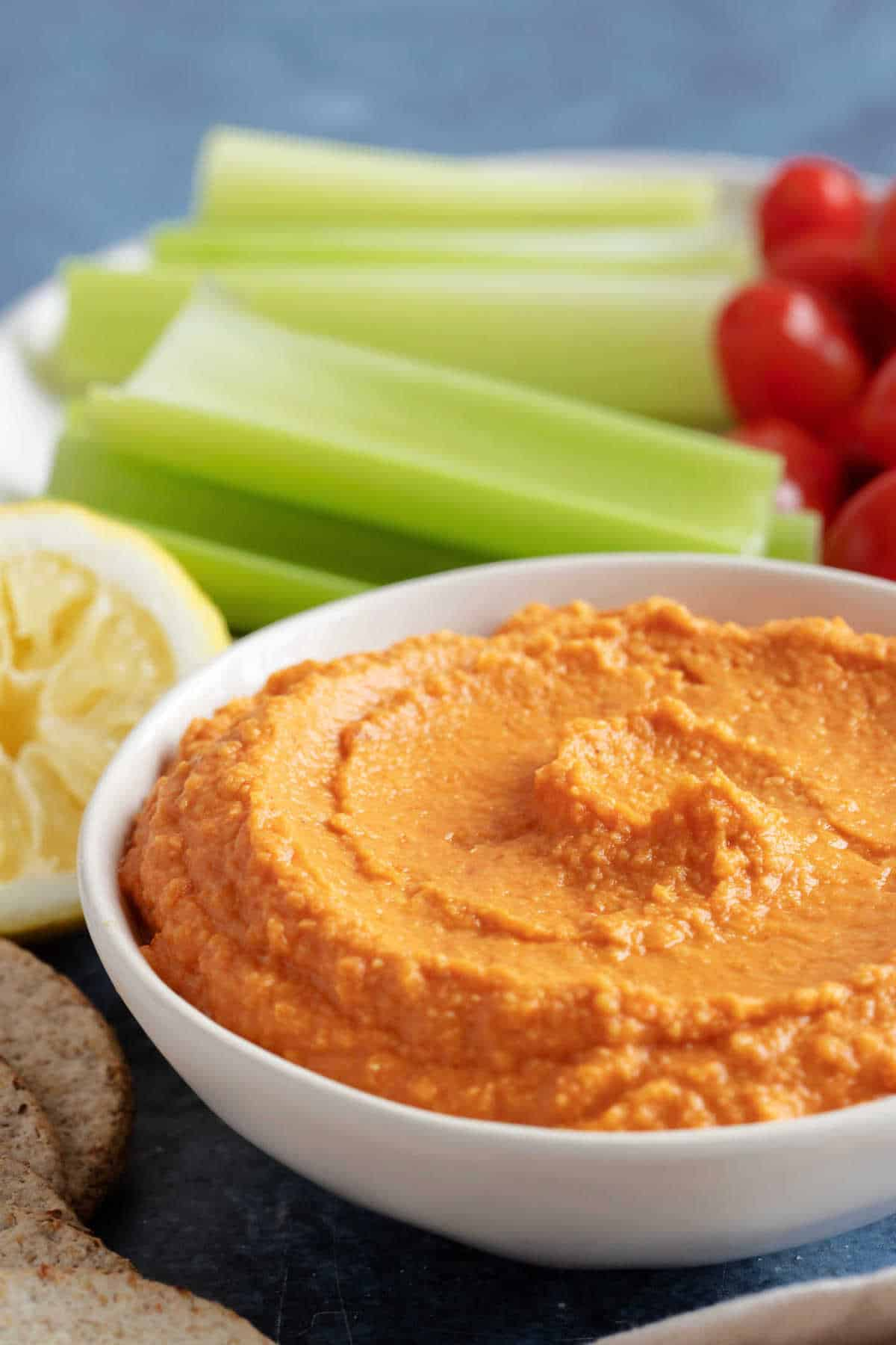 Roasted red pepper hummus in a white bowl.