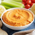 Roasted red pepper hummus with celery sticks.