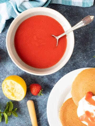 Strawberry coulis in a bowl with pancakes and yogurt.