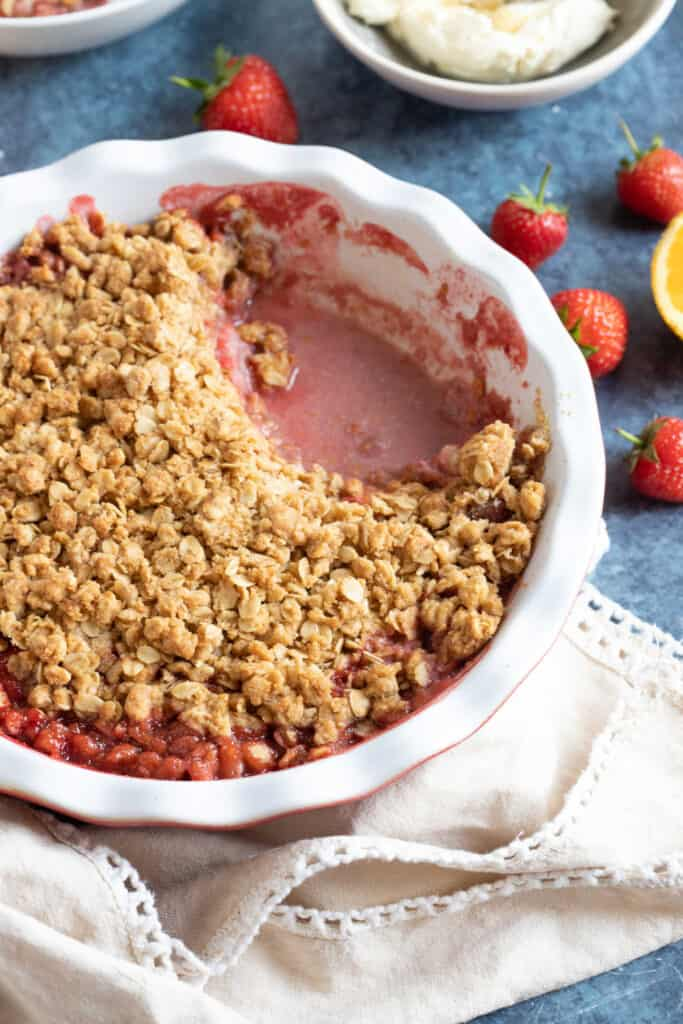 Strawberry crumble in a pie dish with cream.