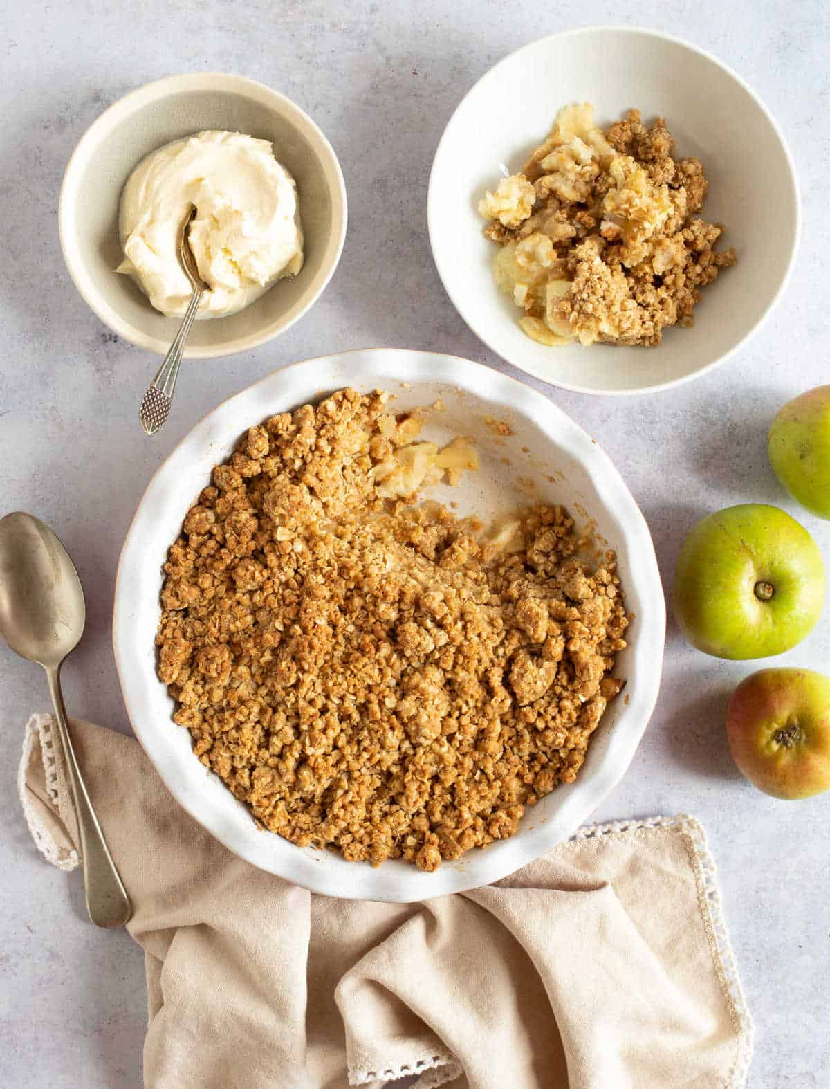 Easy cinnamon apple crumble in a red pie dish with whipped cream.