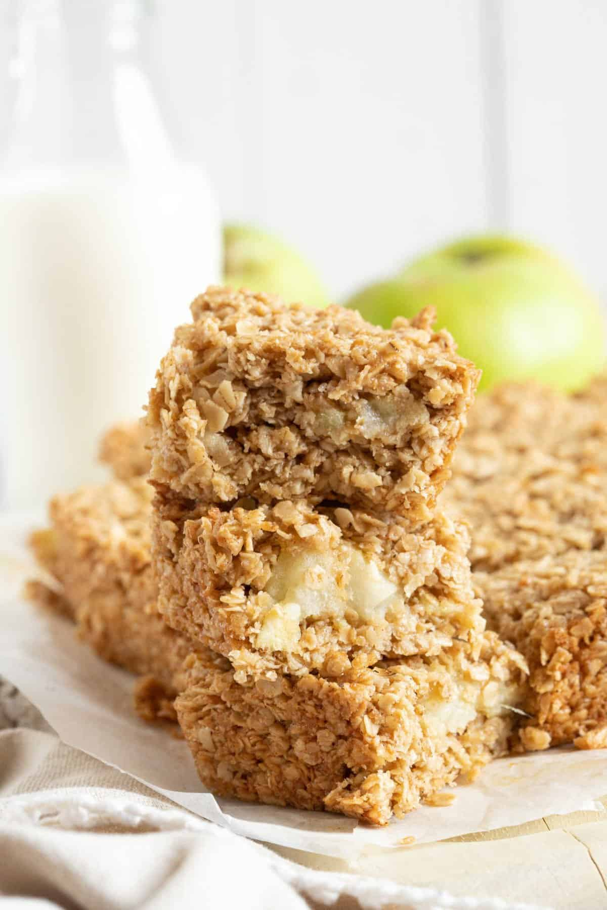 A stack of apple flapjacks with a glass of milk.