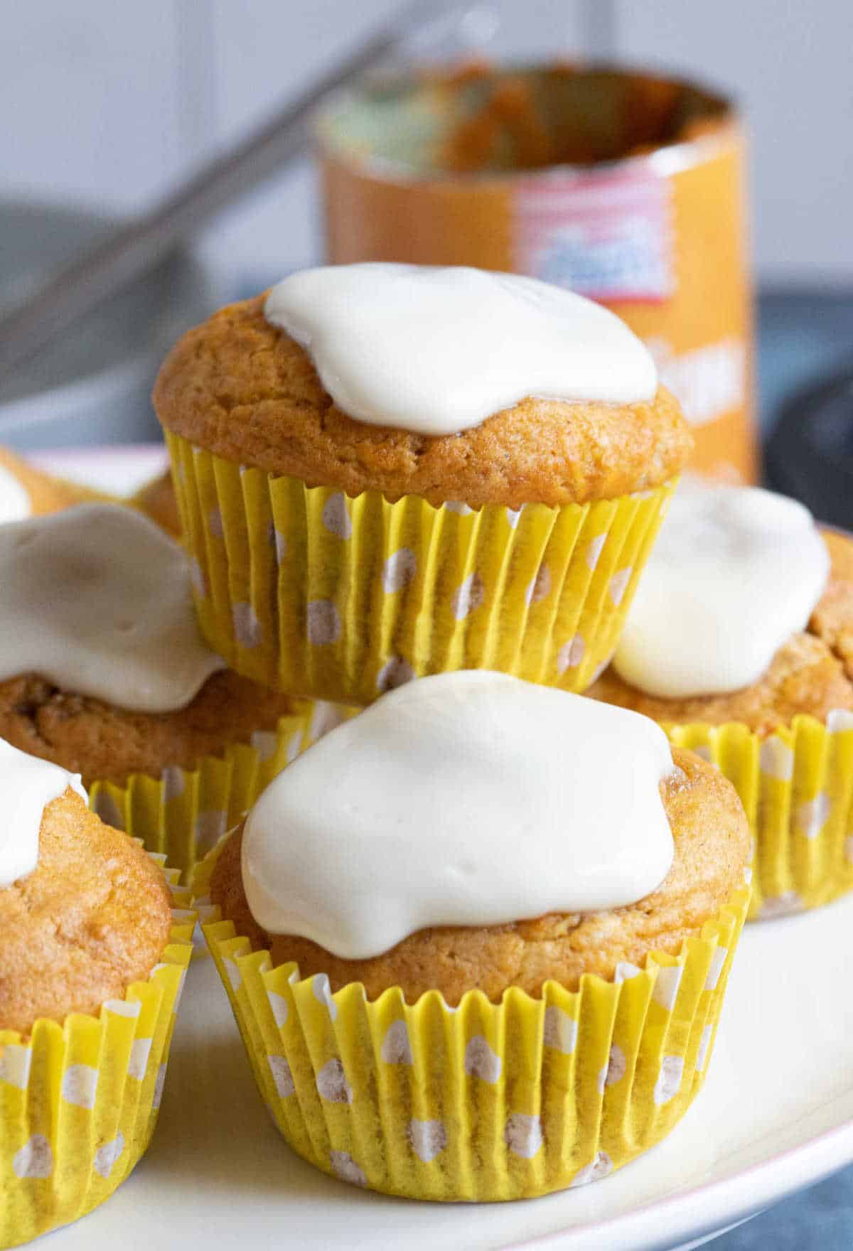 Spiced pumpkin muffins with cream cheese frosting on a cake stand.